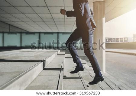 Businessman running fast upstairs. Horizontal outdoors shot. Royalty-Free Stock Photo #519567250