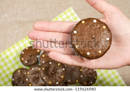 Hand of a woman holding a chocolate muffin. Close up on a freshly baked cacao muffin with candy on top. #519626980