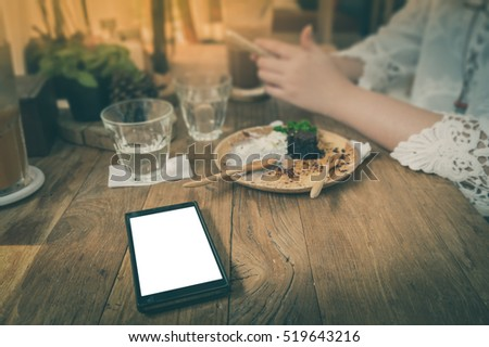 Mobile phone with blank area on touch screen on rustic wood table in cafe. Hipster human role lifestyle concept with technology processed with vintage filter effect #519643216