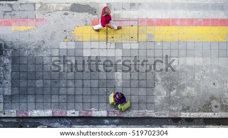 On street walk in top view man and woman with shopping bags stand on square block pedestrian walk way with yellow and red line for guide blind people walk (aerial city street view) #519702304