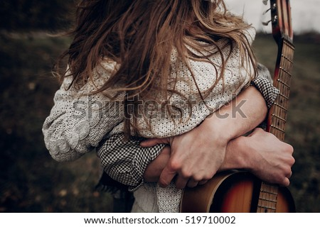 man with guitar hugging his boho gypsy woman closeup in windy field. atmospheric sensual moment. stylish hipster couple in fashionable look. rustic wedding concept #519710002