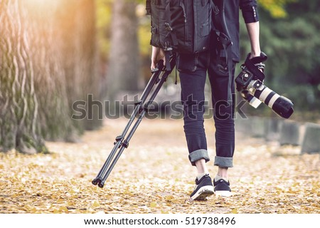 professional photographer with camera and tripod in autumn. Vintage tone. #519738496