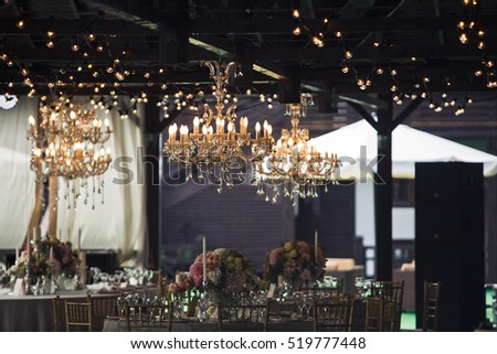 Rich golden chandeliers hang above a wooden ceiling over restaurant's tables #519777448