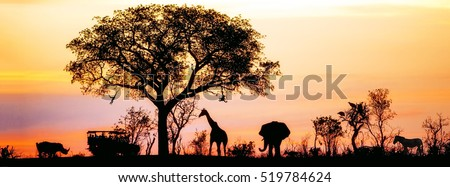Silhouette of African safari scene with animals and vehicle Royalty-Free Stock Photo #519784624