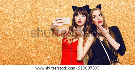 Two women having  great time together, making self portrait , use carnival funny paper glasses, wearing  elegant evening dress. Friends celebrating  new year or birthday party. Space for text.