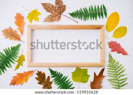 Autumn composition of colorful leaves and picture frame on white wooden background. Top view, flat lay, copy space. Thanksgiving day concept.