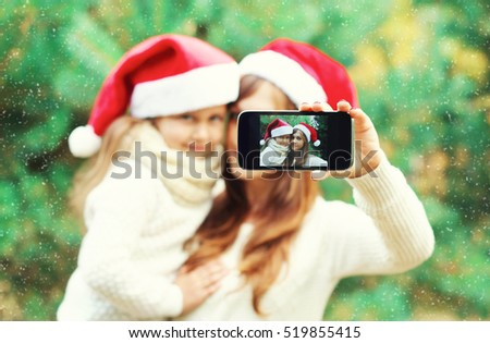 Christmas mother and child taking picture self portrait on smartphone together, closeup, blurred background, over snowflakes