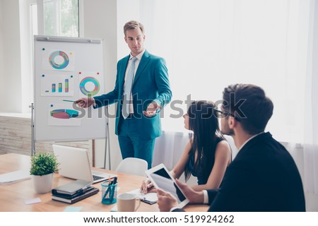 Young manager presenting whiteboard to his colleagues about financial growth Royalty-Free Stock Photo #519924262