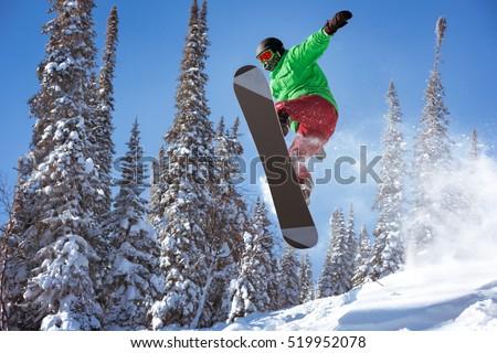 Snowboarder jumps in forest. Freeride snowboarding in Sheregesh ski resort