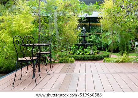 Black chair in wood patio at green garden with fountain in house. Outdoor garden. #519960586