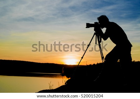 Silhouette of a photographer like to travel and photography, taking pictures of the beautiful moments during the sunset ,sunrise.