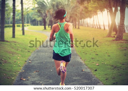 Young fitness sportswoman runner running on tropical park trail Royalty-Free Stock Photo #520017307