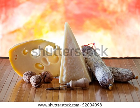 Cheese and salami on a wooden surface with colored background #52004098