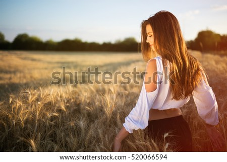 Beautiful carefree woman in wheat meadow #520066594