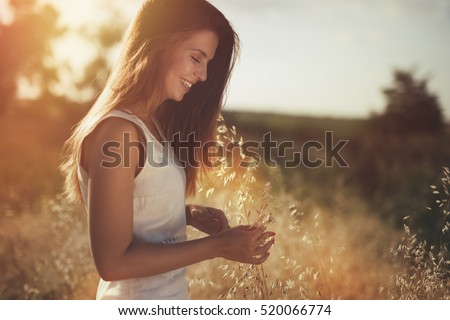 Beautiful carefree woman in fields being happy outdoors #520066774