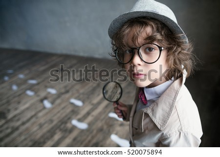 Little detective with a magnifying glass Royalty-Free Stock Photo #520075894