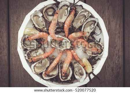 Plate with seafood - oysters and shrimps on wooden background. Toned with sepia boho style colors. Seafood concept.  #520077520
