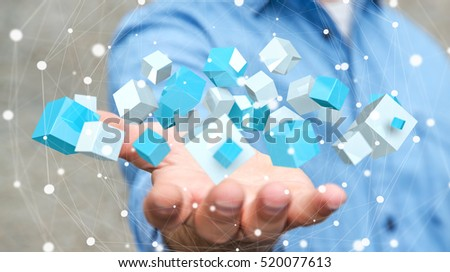 Businessman on blurred background holding flying blue shiny cube 3D rendering