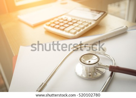 Selective focus Health care costs concept picture : Stethoscope and calculator on a medical chart ,symbol for health care costs or medical insurance with effect light added.