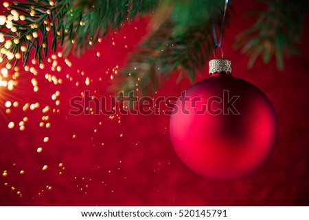 Red christmas decorative ball on the xmas tree on glitter bokeh background with twinkle lights. Merry christmas card. Winter holiday theme. Happy New Year. #520145791