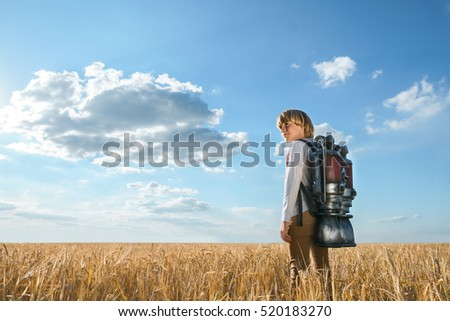 Boy with a backpack in wheat field #520183270