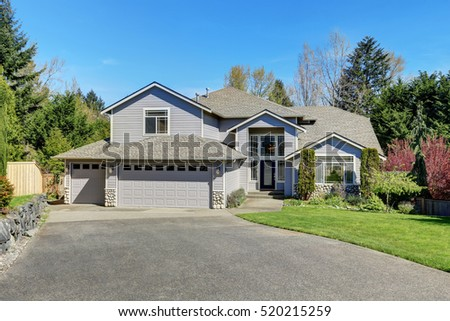 Traditional blue home exterior in Puyallup with wood siding and elegant front door. Northwest, USA #520215259