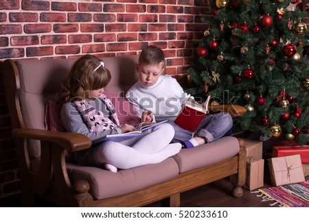 Boy and girl reading book on the sofa near the Christmas tree #520233610