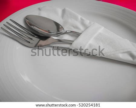 Closeup fork and spoon wrapped in tissue paper on a white plate, Red mat #520254181