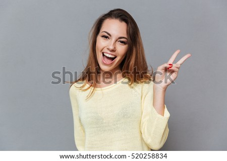 Portrait of a smiling happy woman showing victory sign and looking at camera isolated on the gray background #520258834