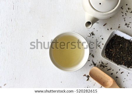 cup with green tea and teapot on white wooden table background. over light #520282615