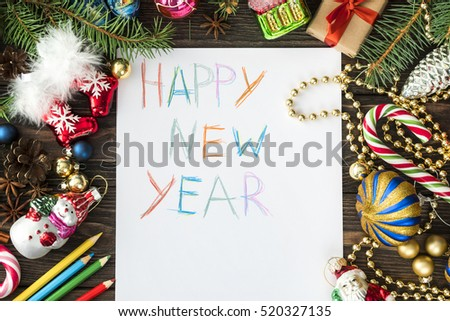 wish card or letter to santa written by kid on wooden desk with many colorful Christmas and new year decoration  #520327135