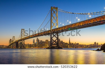 Classic panoramic view of famous Oakland Bay Bridge with the skyline of San Francisco in the background illuminated in beautiful twilight after sunset in summer, California, USA #520353622
