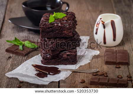 Delicious chocolate brownie with mint on wooden table. #520353730