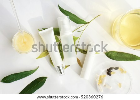 Cosmetic bottle containers with green herbal leaves, Blank label for branding mock-up, Natural beauty product concept. Royalty-Free Stock Photo #520360276