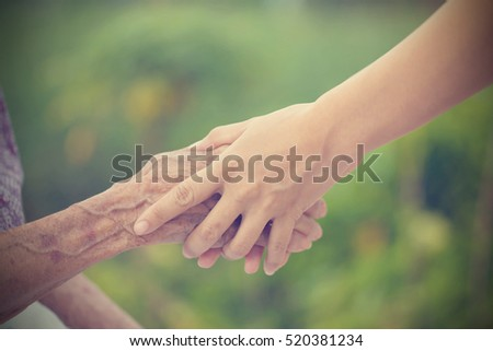 Old and young holding hands on light background, vintage tone. #520381234