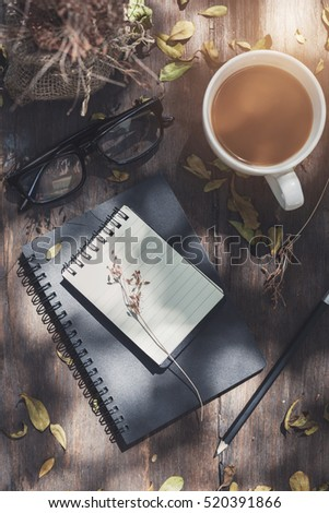 Notebook with cup of coffee on wooden table in the garden, Vintage tone #520391866