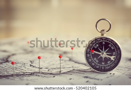 Magnetic compass on a world map conceptual of global travel , tourism and exploration. Macro photo. Royalty-Free Stock Photo #520402105