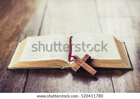 the wooden cross over opened bible on wooden table with window light, vintage tone