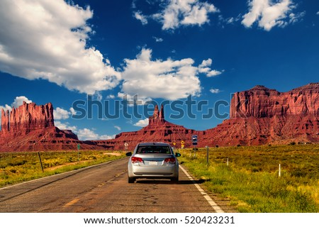 Highway in Monument Valley, Utah / Arizona, USA - Picture with road and cars driving towards the hills. Photo made during a road trip throughout the western states. #520423231