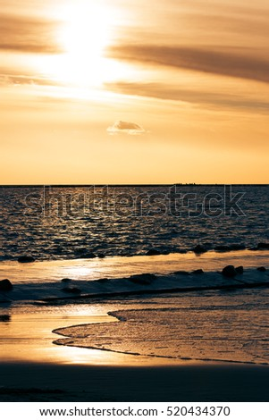 Vertical view of golden sunset at Baltic sea shore #520434370