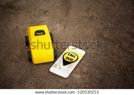 Yellow toy taxi cab and smartphone on ground background. Taxi service application on phone screen. #520530253