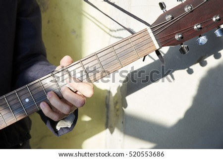 Close-up of a young musician strumming his guitar. #520553686