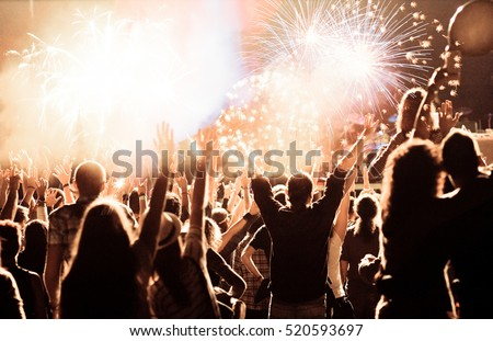 cheering crowd watching fireworks at New Year - holiday celebration background #520593697