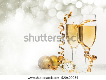 Glasses with champagne and golden Christmas balls against holiday lights - New Year background #520600084