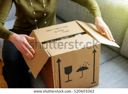 Woman unpacking unboxing cardboard carton box with protective foam pads inside after buying ordering online via internet a present good #520601062