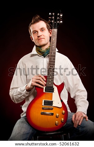 man with a guitar on a dark red background #52061632