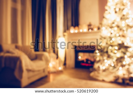 Beautiful holiday decorated room with Christmas tree armchair and fireplace at night. Led lighting, cozy home scene. Nobody there. Out of focus shot for holiday background.