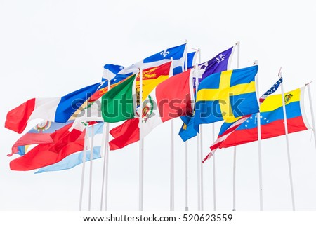 International flags of different countries are hanging on poles in the wind