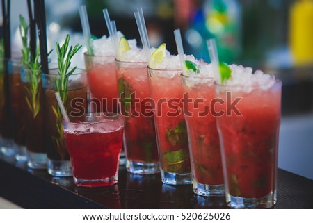 Beautiful row line of different colored alcohol cocktails on a party, martini, vodka,and others on decorated catering bouquet table on open air event, picture with beautiful bokeh  #520625026