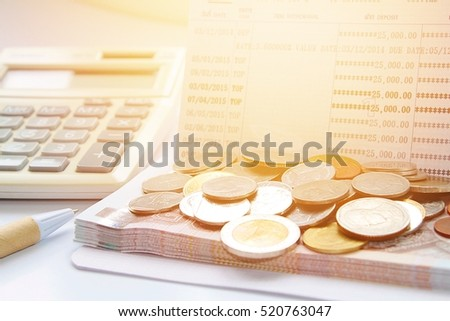 Business, finance, investment, savings or mortgage background concept ; Coins, Thai money, pen, calculator and savings account passbook on white background #520763047
